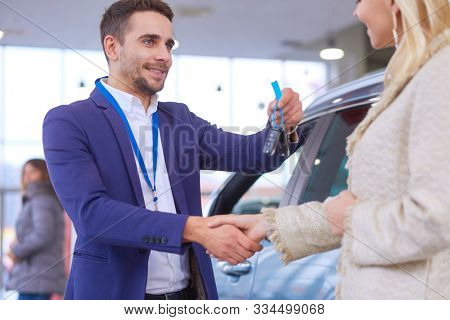 Car salesman sells a car to happy customer in car dealership and hands over the keys.