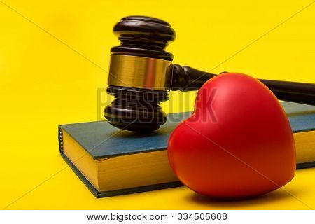Medical Malpractice Lawsuit Concept Showing A Gavel, A Law Book And A Heart On A Yellow Background