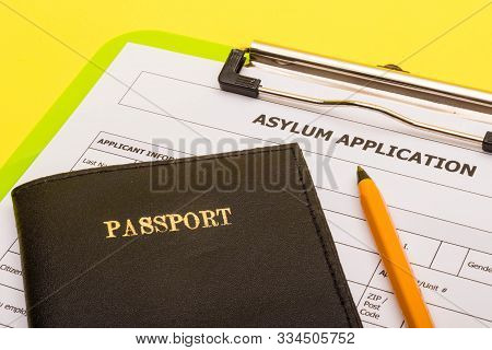Asylum Concept Showing An Application Form For Asylum On A Yellow Background With A Pen And A Passpo