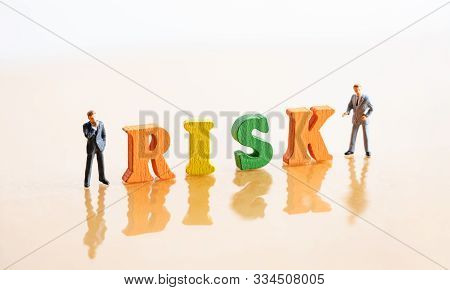 Miniature People: Businessmans And Wood Word Block Risk. Risk Management Concept.