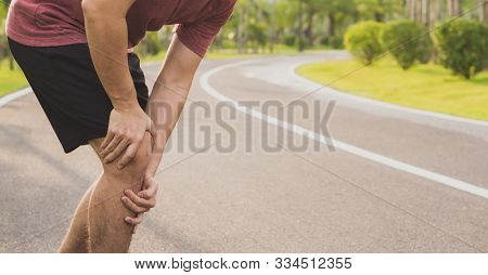 Knee Injuries. Young Sport Man Holding Knee With His Hands In Pain After Suffering Muscle Injury Dur