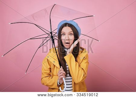 Pretty Surprised Girl In A Gentle Blue Barret, A Striped Blouse And A Yellow Rain Jacket Smiles Cute