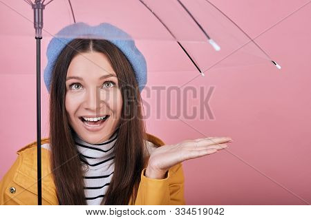 Pretty Happy Cheerful Girl In Gentle Blue Barret, Striped Blouse And A Yellow Rain Jacket Against Pi