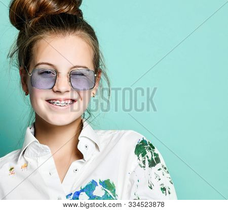 Portrait Of Smiling Young Woman Girl With Braces In White Shirt With Colorful Paint Stains And Recta