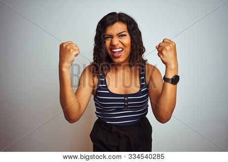Transsexual transgender woman wearing striped t-shirt over isolated white background angry and mad raising fists frustrated and furious while shouting with anger. Rage and aggressive concept.