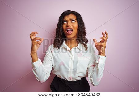 Transsexual transgender businesswoman standing over isolated pink background crazy and mad shouting and yelling with aggressive expression and arms raised. Frustration concept.