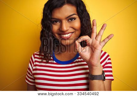 Transsexual transgender woman wearing stiped t-shirt over isolated yellow background doing ok sign with fingers, excellent symbol
