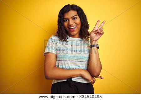 Beautiful transsexual transgender woman wearing t-shirt over isolated yellow background smiling with happy face winking at the camera doing victory sign. Number two.