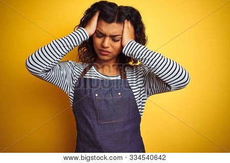 Young transsexual transgender chef woman wearing apron over isolated yellow background suffering from headache desperate and stressed because pain and migraine. Hands on head.