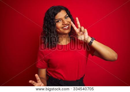 Beautiful transsexual transgender woman wearing t-shirt over isolated red background smiling looking to the camera showing fingers doing victory sign. Number two.