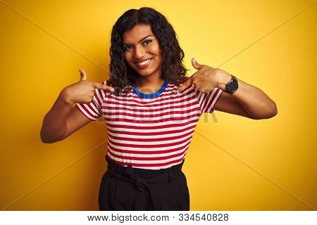 Transsexual transgender woman wearing stiped t-shirt over isolated yellow background looking confident with smile on face, pointing oneself with fingers proud and happy.