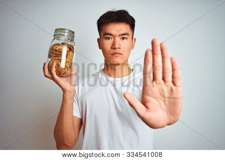 Young asian chinese man holding jar of cookies standing over isolated white background with open hand doing stop sign with serious and confident expression, defense gesture