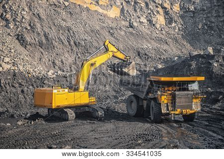 Hydraulic Excavator Loads Coal Into Body Of Large Yellow Mining Truck. Open Pit Mine Industry For An