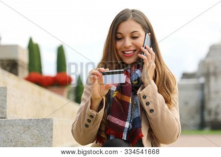 Smiling Woman Sitting Outdoors Looking At Number On Credit Card And Confirm Purchase Via Telephone C