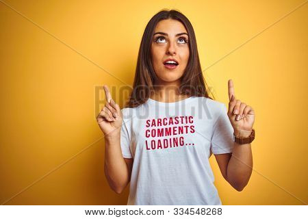 Beautiful woman wearing fanny t-shirt with irony comments over isolated yellow background amazed and surprised looking up and pointing with fingers and raised arms.