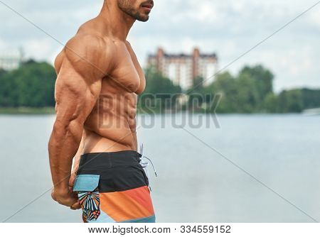 Powerful, Athletic Strong Man Showing Naked Muscular Body. Handsome Bodybuilder Posing Near Lake On