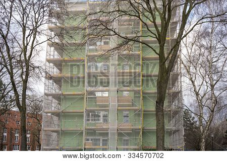 Construction Site, Skyscraper With Scaffolding And Trees