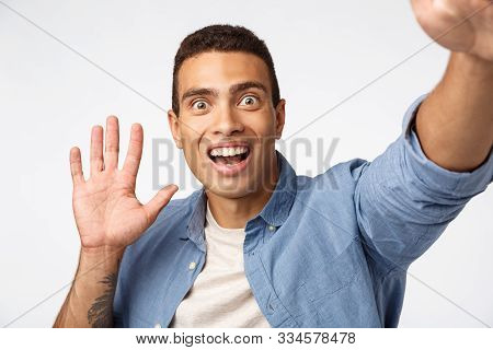 Surprised And Impressed Man Didnt Expact See Someone As Holding Camera, Waving Hand In Hello Or Hi G