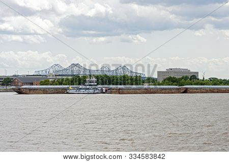 Barges And Tugboat On Mississippi River At Algiers Point With Crescent City Connection Bridge Behind