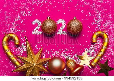 Christmas Card With The Inscription 2020 Of Sparkles And Balls. Pink Background, Gold Decorations Fo