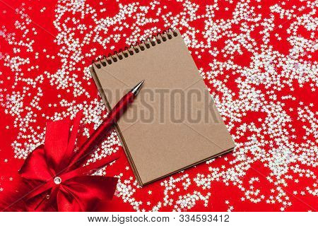Craft Notebook With A Beautiful Pen With Feather On A Red Background With Sparkles. Christmas , Fest
