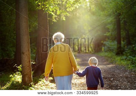 Elderly Grandmother And Her Little Grandchild Walking Together In Sunny Summer Park. Grandma And Gra