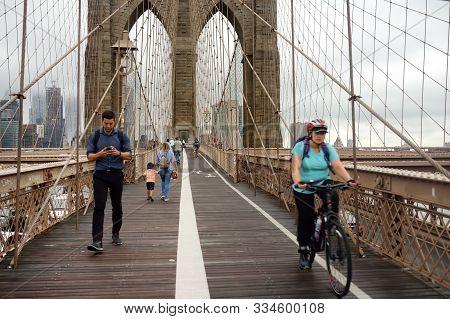 New York, Usa - 12 July 2019: Pedestrians Walk Over The Brooklyn Bridge At Sunset. Traffic Of People