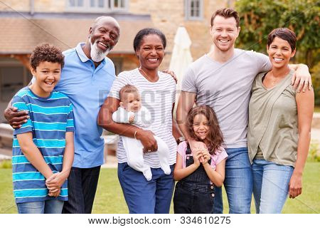 Portrait Of Smiling Multi-Generation Mixed Race Family In Garden At Home