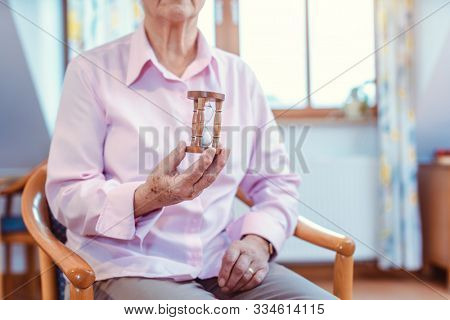 Senior in nursing home holding a hourglass - time is running up quickly