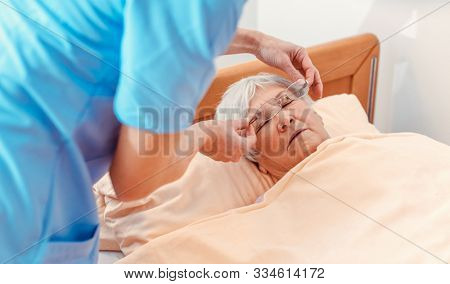 Nurse taking care of sleeping senior woman in the nursing home getting her glasses off