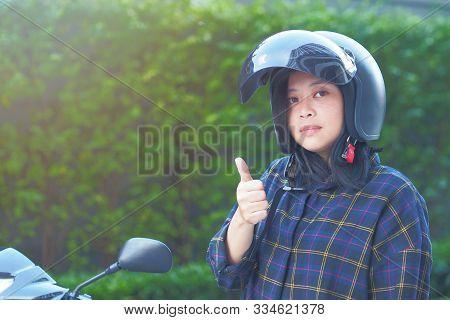 A Young Woman Fastening Or Wearing Her Motorbike Helmet With Blur Fukien Tea Tree Carmona Retusa Gre