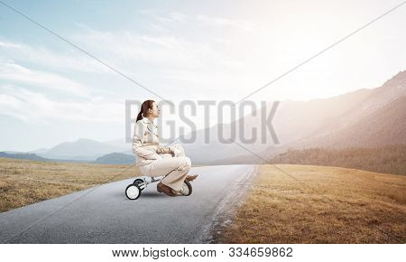 Caucasian Woman Riding Kids Bicycle On Asphalt Road. Young Employee In White Business Suit Biking Ou