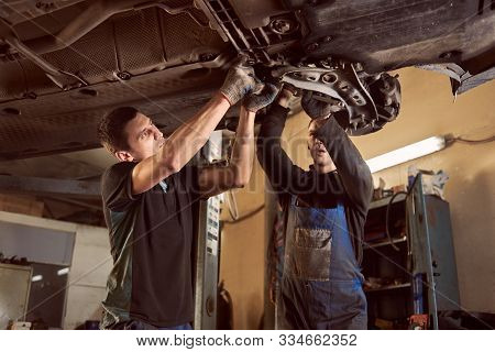 Transmission Checking And Repairing. Two Proficient And Concentrated Auto Mechanics In Dirty Coveral