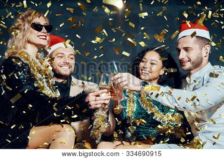 Multiethnic Happy Friends Toasting With Champagne Celebrating Christmas Or New Year, Congratulating