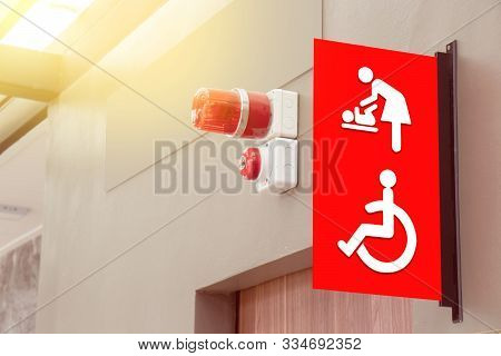Mother's Room And Disabled Toilet Sign On Red Tab With Red Siren Light Hang Above The Door Of Public