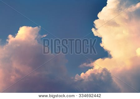 Detail Of White Clouds And Blue Sky In Orange Sunset Light