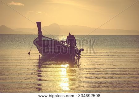 Small Wooden Local Fishing Boat Moored At The Beach In The Morning.