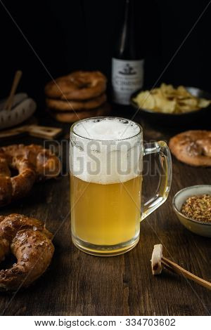 Beer Glass With Pretzels, Bratwurst And Snacks On Rustic Wooden Table