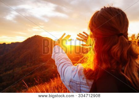 Carefree hipster girl enjoying sunset on top of mountain. Image of freedom concept. Model meditates while travel holidays vacation outdoors. Photo toned style instagram filters, vintage effect.