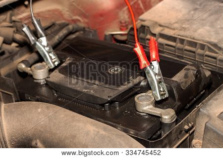 Charging An Old Car Battery In A Dirty Engine. Preparing The Car For Winter Season. Faulty Car Batte