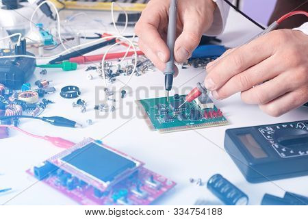 Technician Man Hands Using Digital Multimeter To Check And Measure Electrical Voltage Of Computer Ma