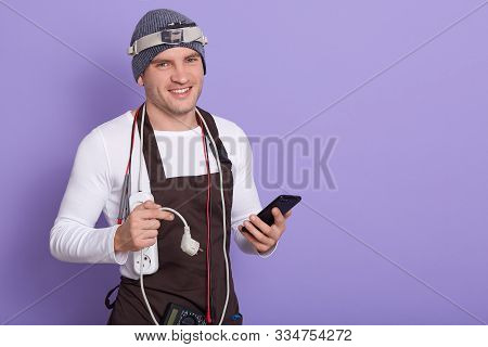 Picture Of Joyful Electronic Engineer Holding Smartphone And Plug, Having Cords And Electronic Equip