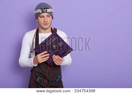 Portrait Of Young Experienced Radiotrician Standing Isolated Over Lilac Background In Studio, Holdin