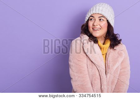Beautiful Astonished Female Wears Pale Pink Faux Fur Coat, Yellow Sweater, White Cap, Looks Smiling