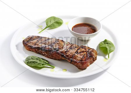 Striploin steak with sauce close up. Grilled beef with basil leaves isolated on white background. Barbeque meat, roasted pork served on plate composition. Traditional New York strip steak