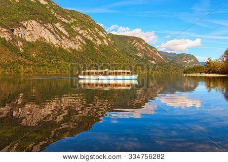 Old Touristic Boat On Bohinj Lake. Panoramic View Of Bohinj Lake With Mountain Range Which Reflected