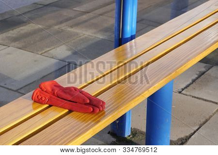 Red Womens Gloves Forgotten On A Bench Or At A Bus Stop On A Warm Sunny Day. Warehouse Or Lost And F