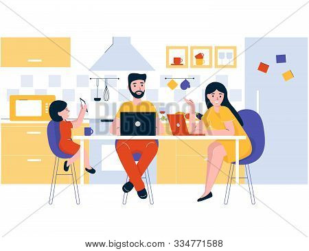 Concept Happy Young Family Sits In The Kitchen At The Table. Dad And Mom Work On The Internet At A L