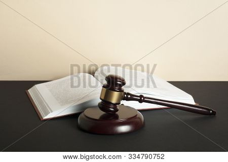 Law Concept. Wooden Judge Gavel And Open Book On Table In A Courtroom Or Enforcement Office.