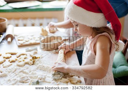 Kids Cooking Christmas Cookies In Cozy Kitchen. Child Prepares Holiday Food For Family. Cute Little